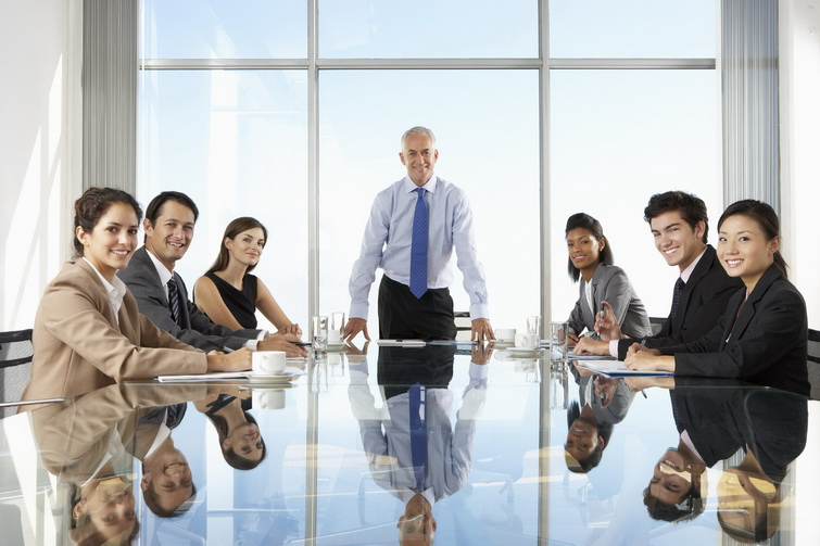 Group Of Business People Having Board Meeting Around Glass Table